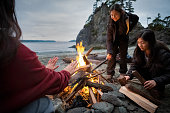 Eurasian Generation Z sisters in winter clothing add kindling to campfire.  Pacific Ocean in background.  Bamfield, Vancouver Island, British Columbia, Canada