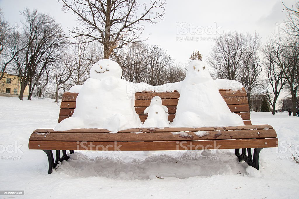 Family of snowman on a bench stock photo