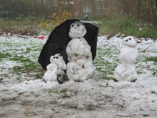 familie van sneeuwmannen hidingunder een paraplu in het Vondelpark in Amsterdam foto