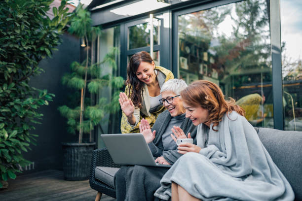 family of three beautiful women having video call on laptop in the home garden. - family gatherings stock pictures, royalty-free photos & images