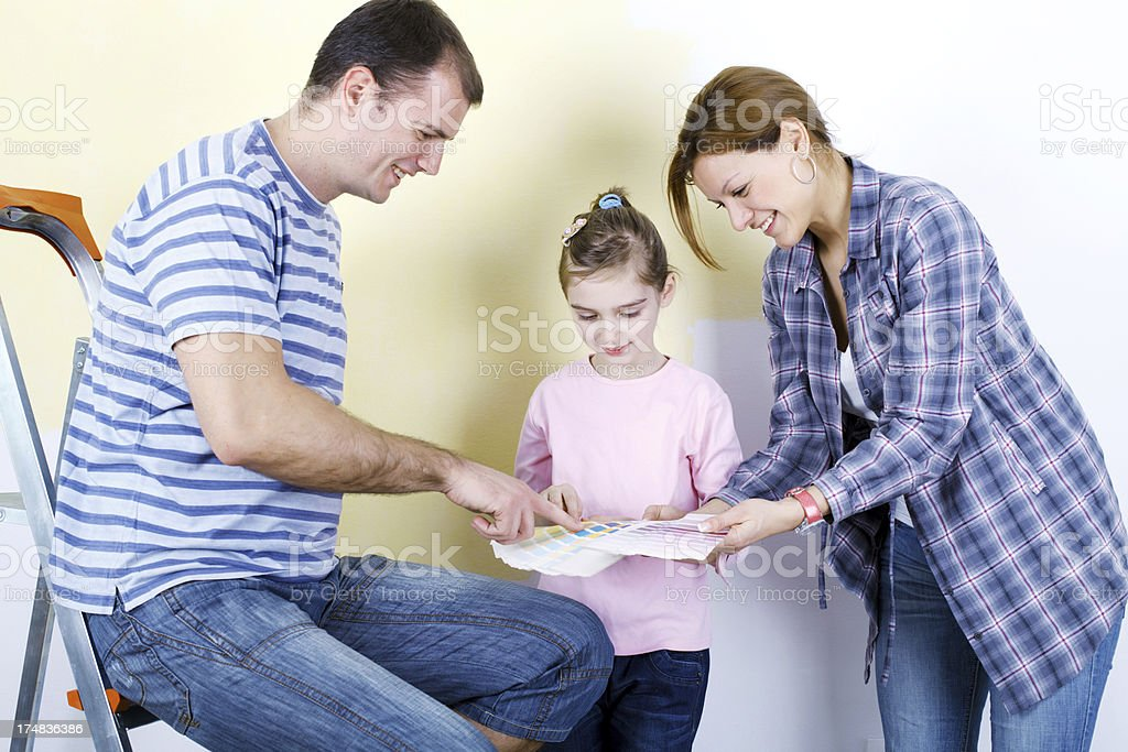 Family of three choosing colors to paint a room. royalty-free stock photo