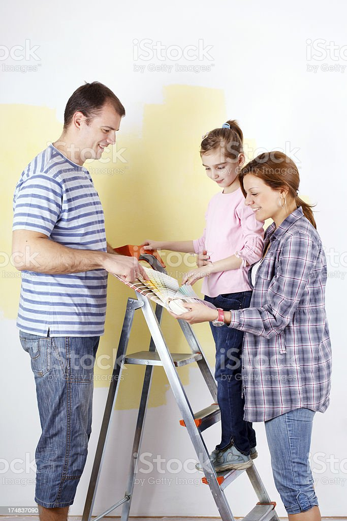 Family of three choosing colors to paint a room royalty-free stock photo