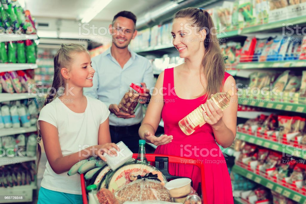 family of three choosing food in the grocery shop - Royalty-free Adult Stock Photo