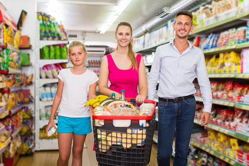 Family Of Three Choosing Food In The Grocery Shop Stock Photo - Download Image Now