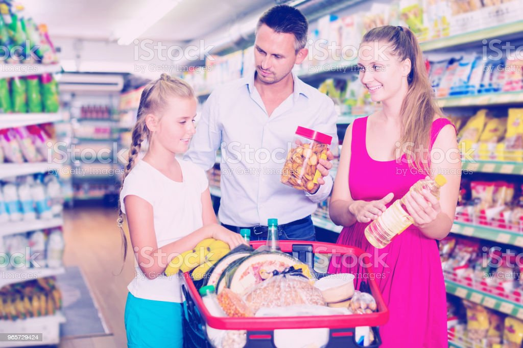 family of three choosing food in the grocery shop - Royalty-free 1910-1919 Foto de stock