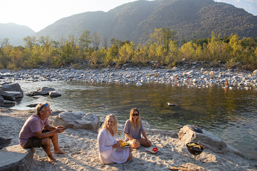 Family of three have bbq dinner on river beach