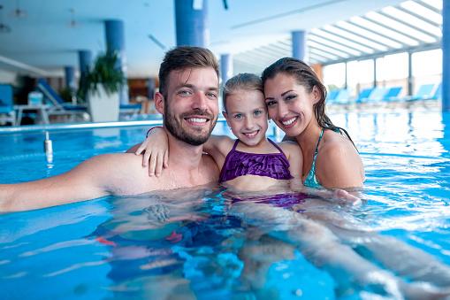 一家三口之家在游泳池裡玩得開心 照片檔及更多 一起 照片