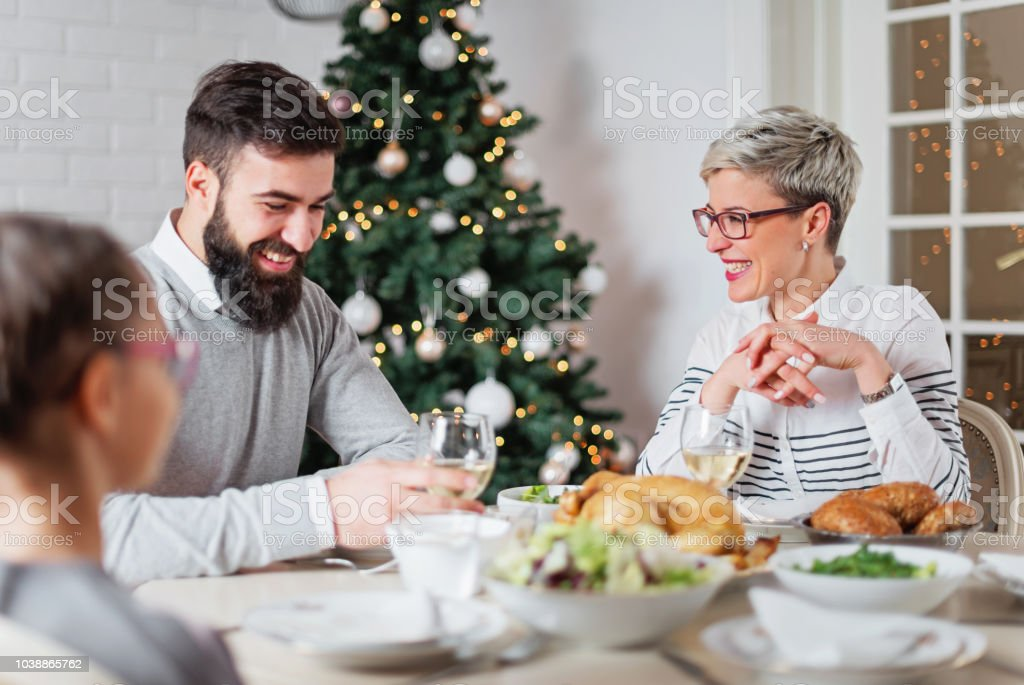 Family of three having lunch for Christmas holidays stock photo
