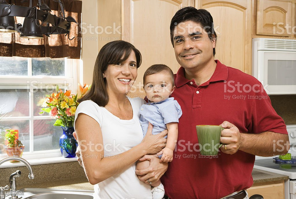 Family of three in kitchen smiling for the picture royalty-free stock photo