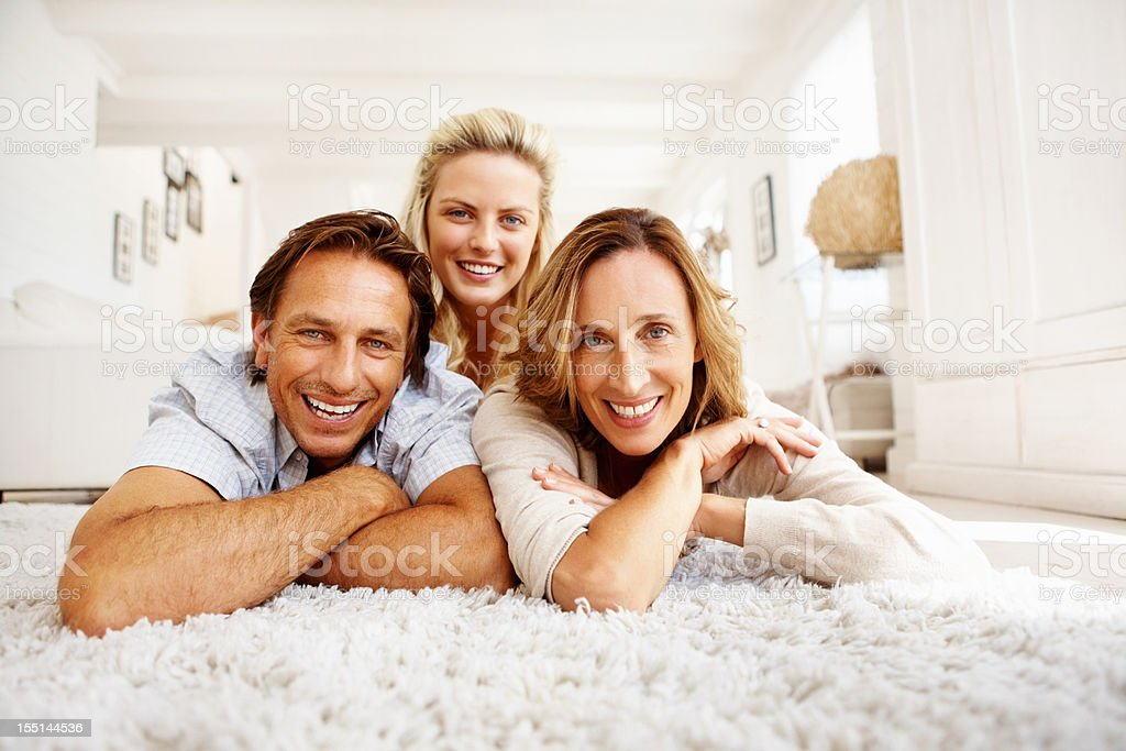 Family of three lying on carpet Portrait of a family of three lying on the carpet and giving you a cute smile 40-49 Years Stock Photo