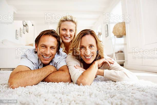 Family Of Three Lying On Carpet Stock Photo - Download Image Now