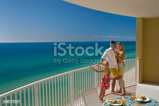 Mom, dad and daughter standing on the balcony overlooking Gulf of Mexico.