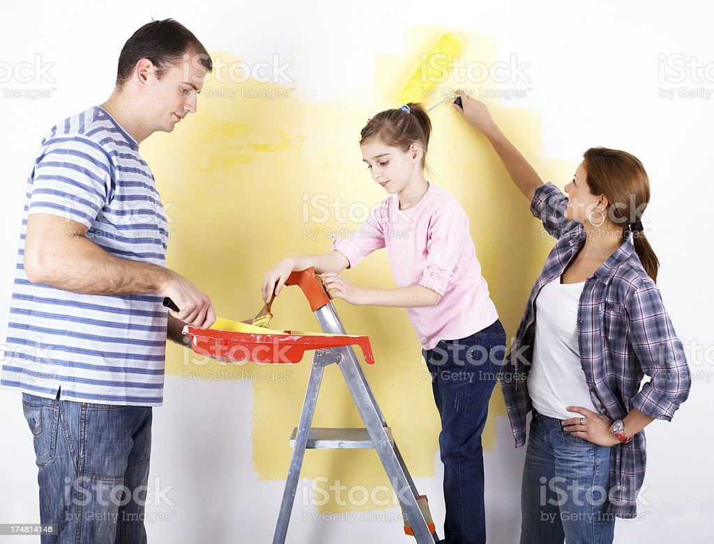 Family of three painting the wall royalty-free stock photo