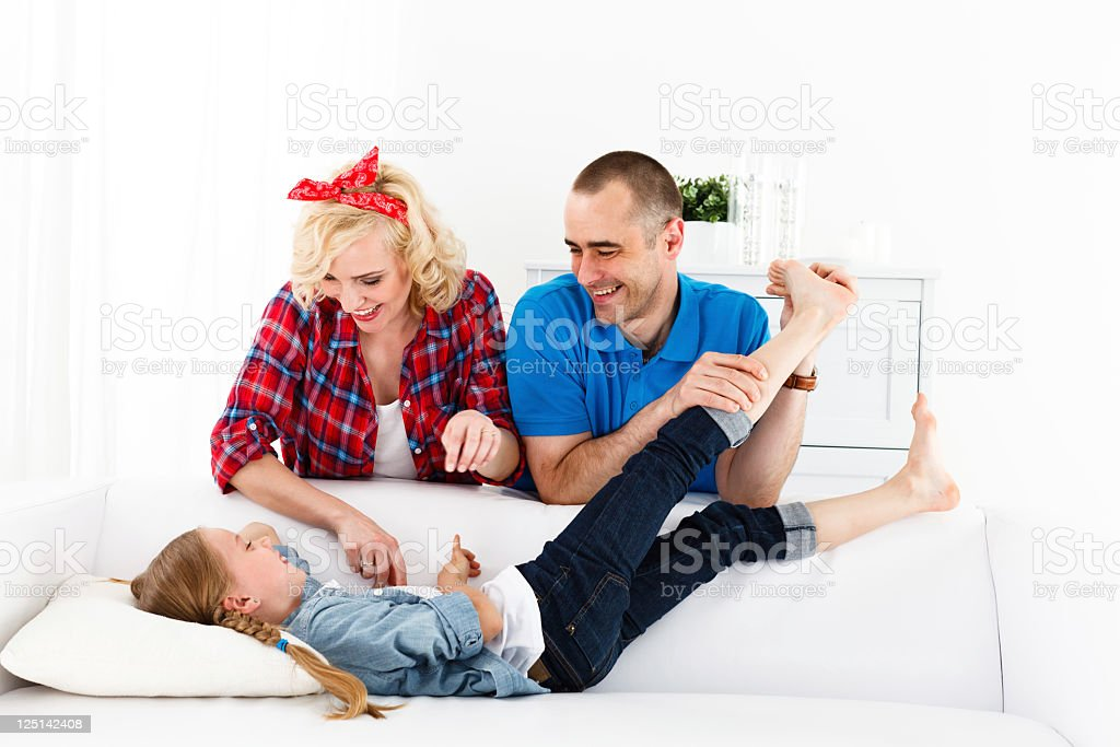 Family of Three, Parents Tickling Their Daughter royalty-free stock photo