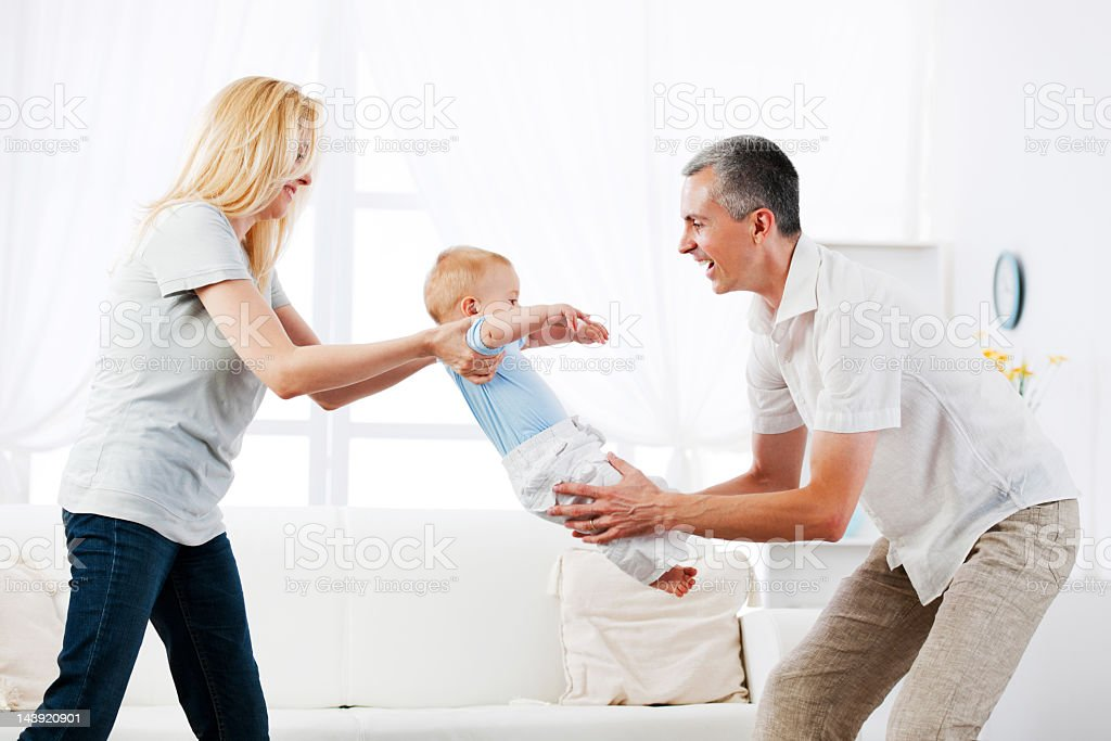 Family of three people enjoying while playing at home. royalty-free stock photo