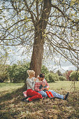 Cheerful young family of three people resting under a tree in spring park