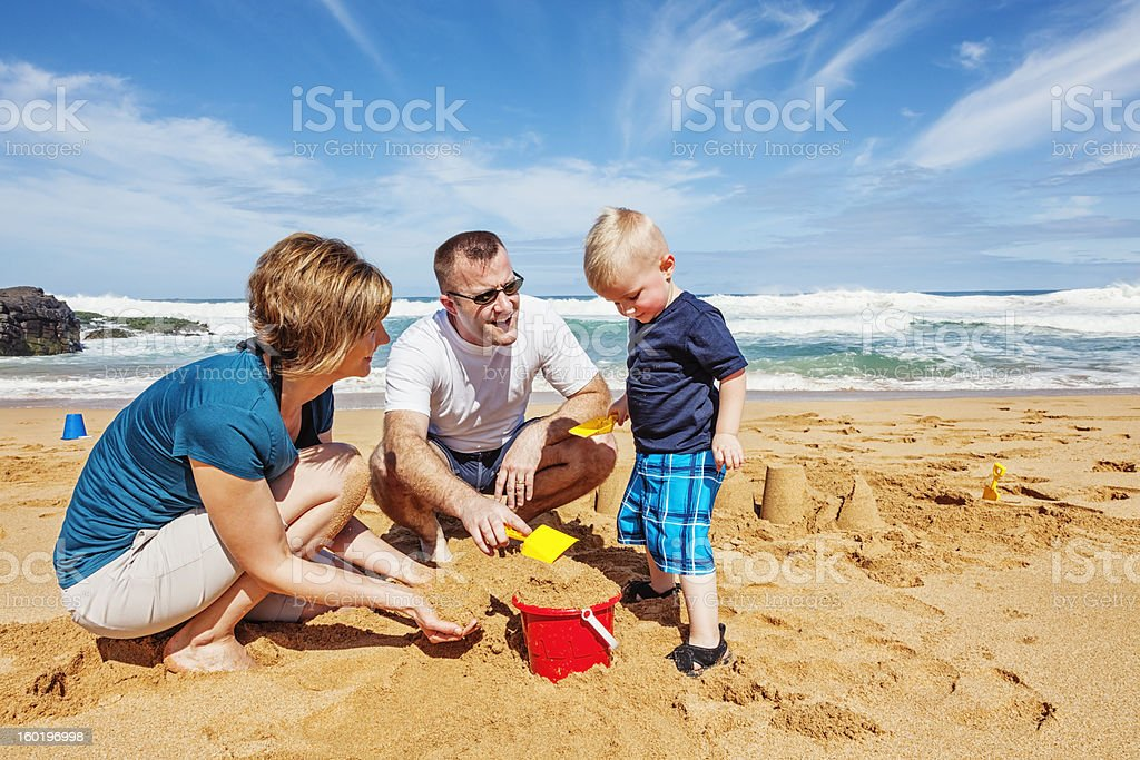 Family of Three Playing on The Beach stock photo