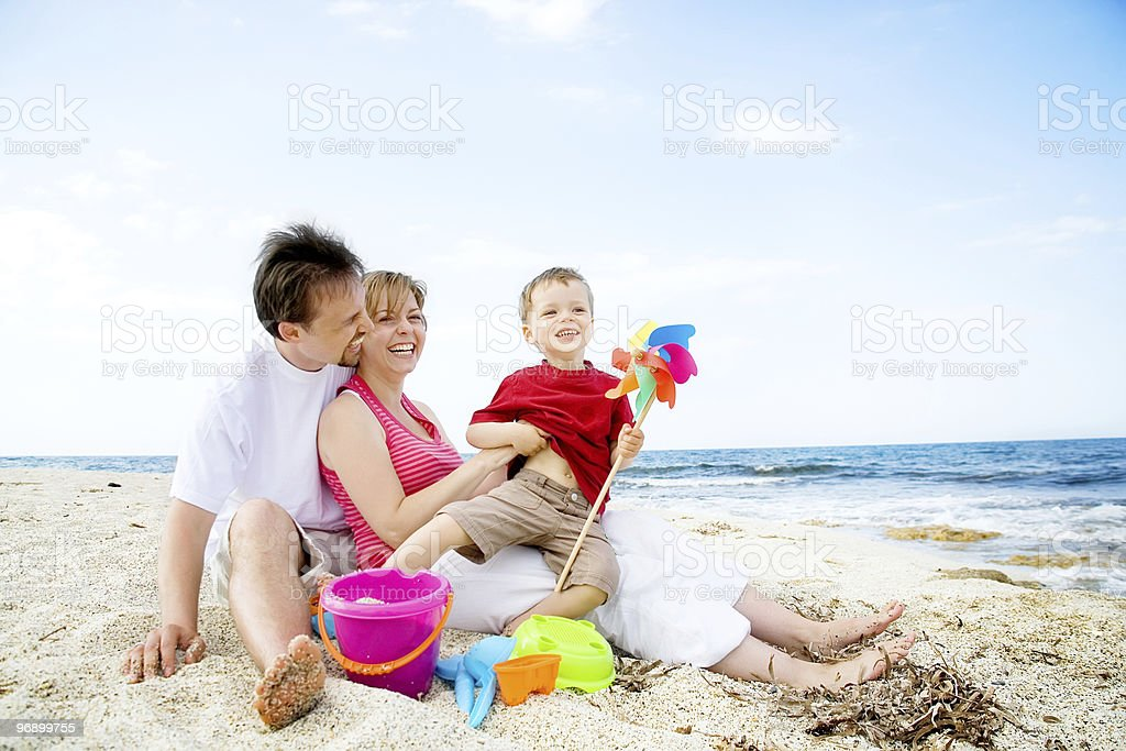 Family of three relaxing and having fun on the beach royalty-free stock photo