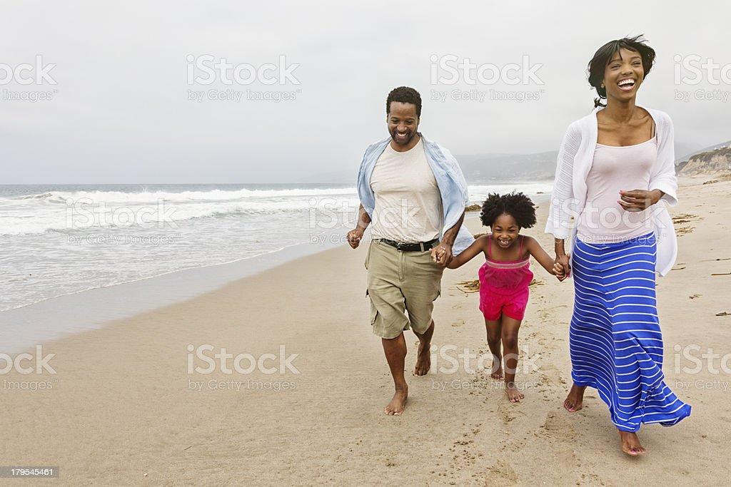 Family of Three Running on The Beach stock photo