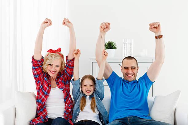 familie sitzt auf sofa mit arme hoch - jubeln mutter shirts stock-fotos und bilder