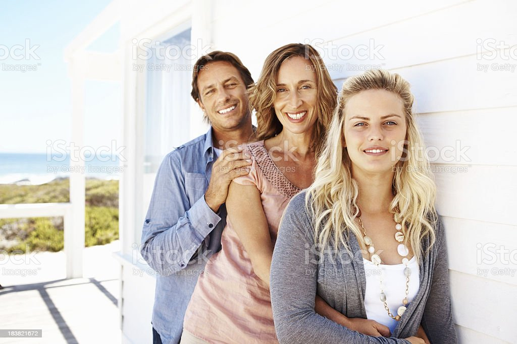 Family of three standing on the porch and smiling royalty-free stock photo