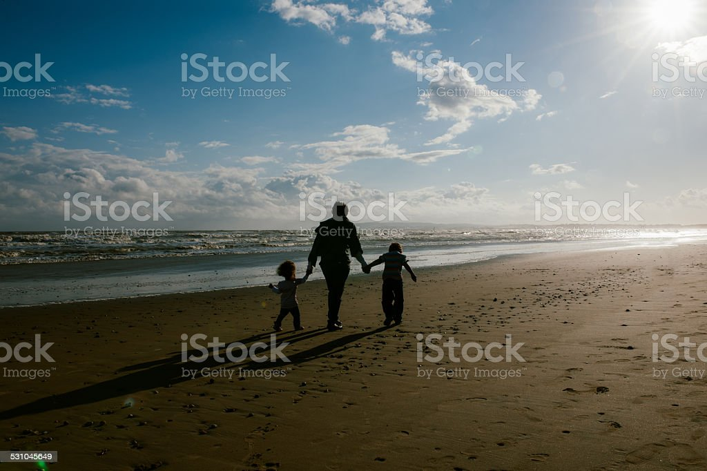 Family Of Three Walking On The Beach At Sunset stock photo