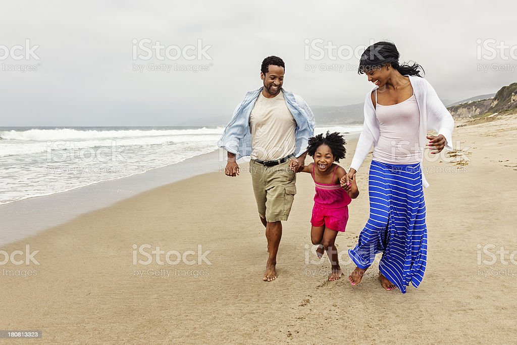 Family of Three Walking on The Beach stock photo