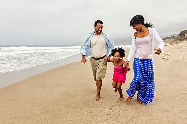 Family of Three Walking on The Beach stock photo