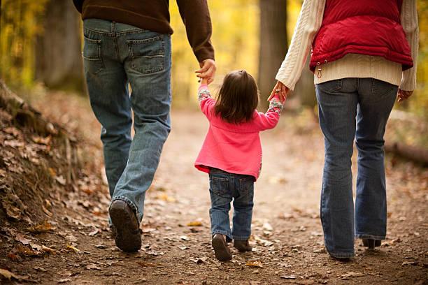 Family of Three Walking on Trail Through Autumn Woods stock photo