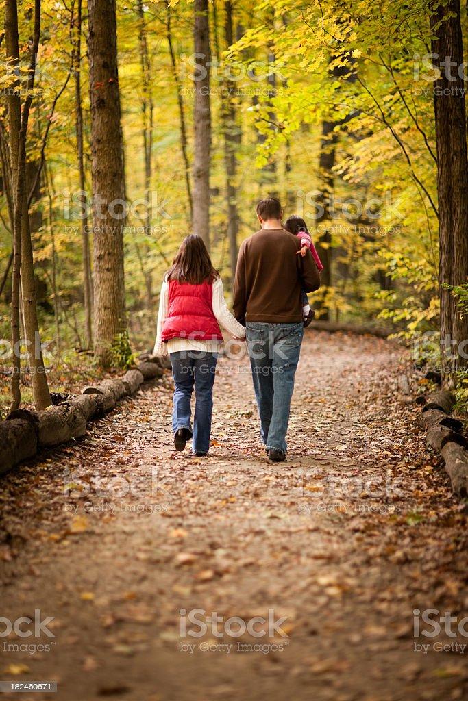Family of Three Walking on Trail Through Autumn Woods royalty-free stock photo