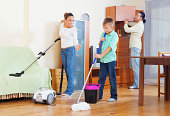 family of three with teenager doing housework with  cleaning equipment
