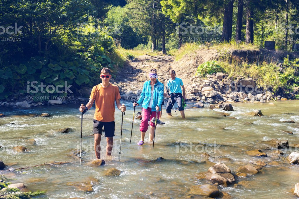 Family of travelers cross the mountain river stock photo