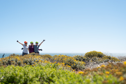 Family of Women Cyclists Celebrating at Cliff Edge, California Coast