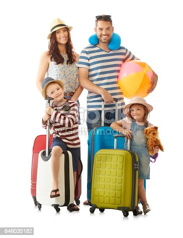 a young family pose with their luggage all set for a summer holiday