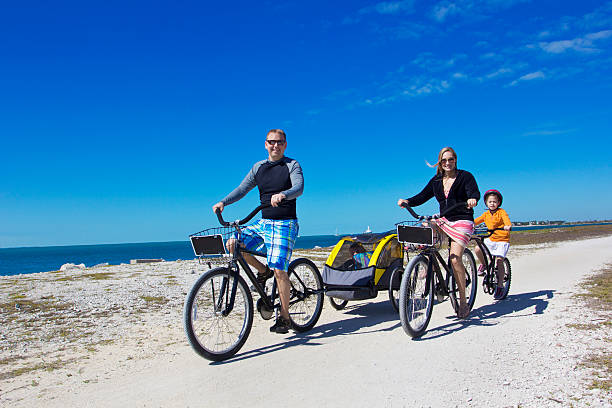 Family on a beach bicycle ride together stock photo
