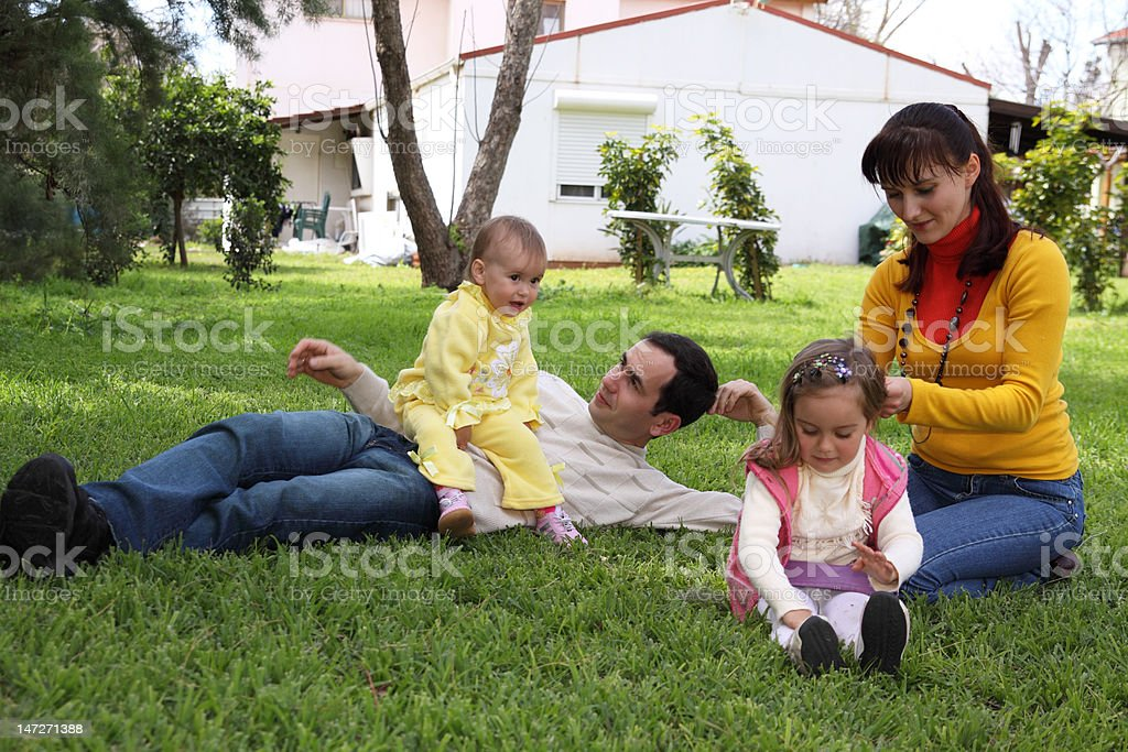 Family on a lawn in front of the house royalty-free stock photo