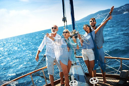 Closeup front view of a senior couple with their son and his fiancee on a sailing cruise across the Mediterranean. They are standing at the bow with their arms raised.