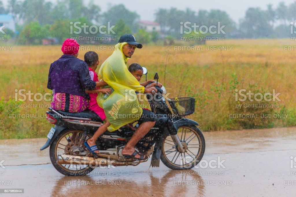 Familie auf einem Roller unter Regen – Foto