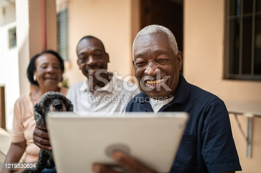 Family on a video calling using digital tablet at home