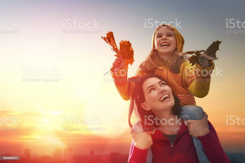 Mother and her child girl playing together on autumn walk in nature...