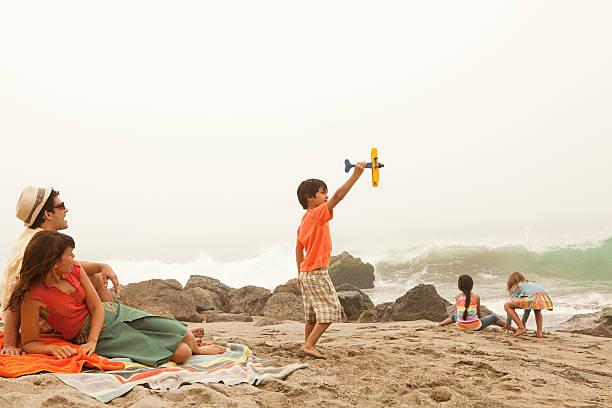 familie am strand, junge spielt mit spielzeug flugzeug - kinder picknick spiele stock-fotos und bilder