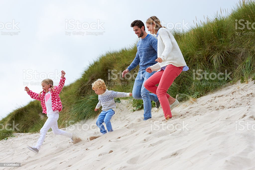 Family On Beach Vacation Running Through Dunes stock photo