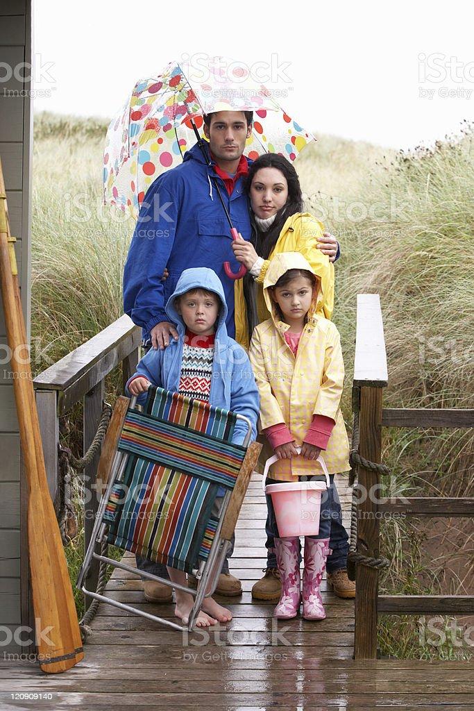 Family on beach with umbrella stock photo