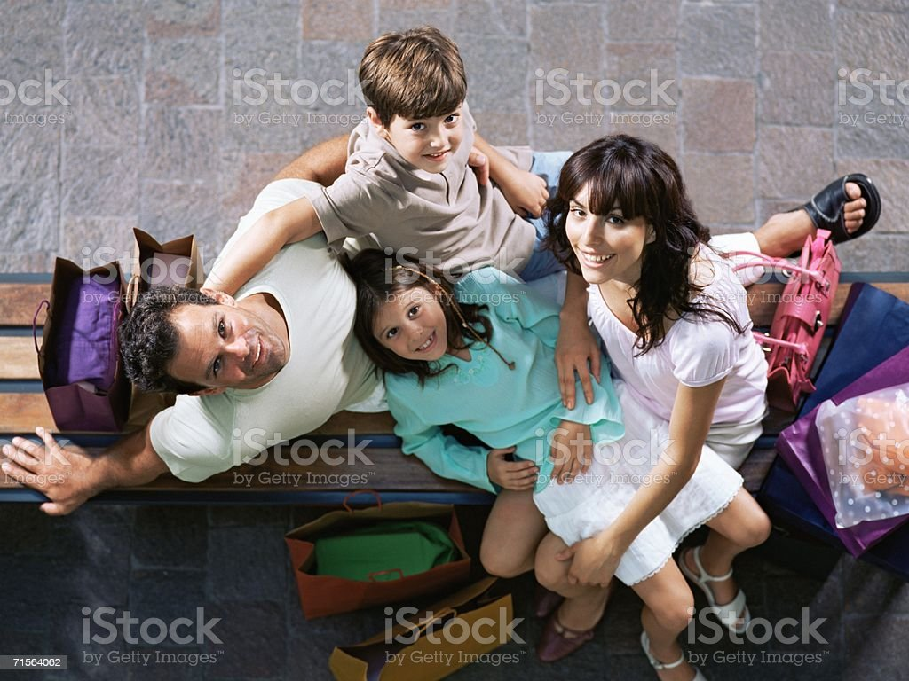 Family on bench with shopping bags royalty-free stock photo