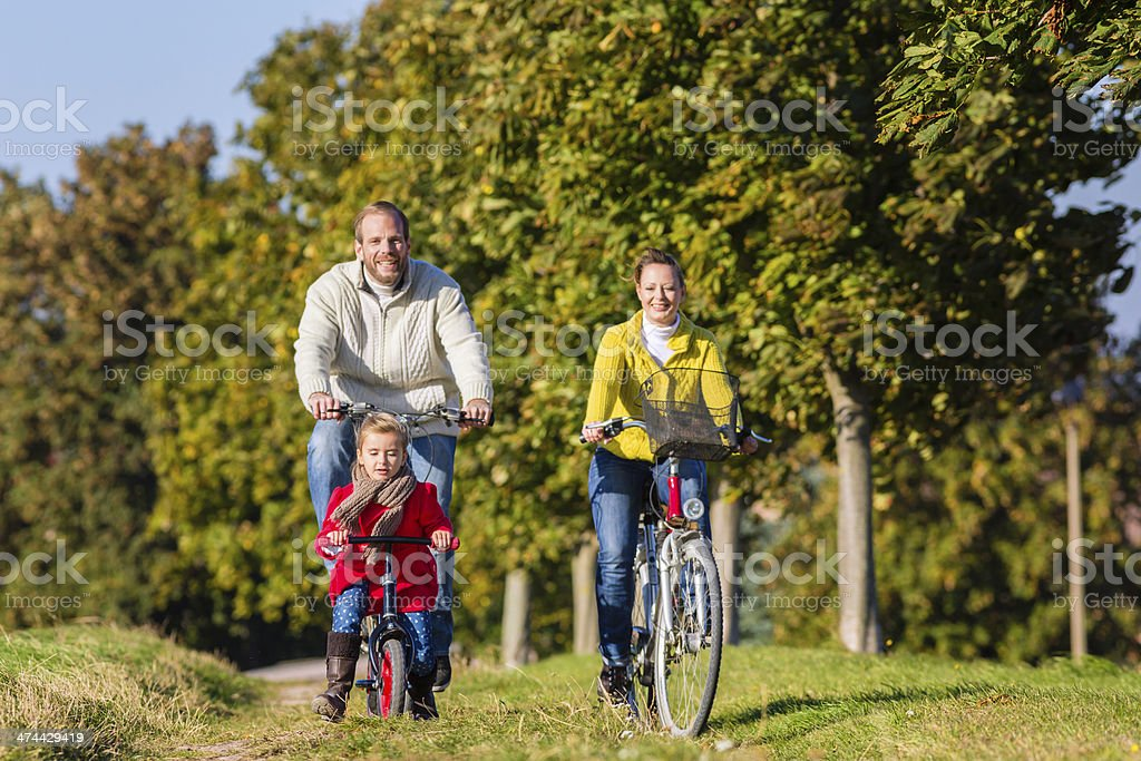 Family on bicycle tour in park stock photo