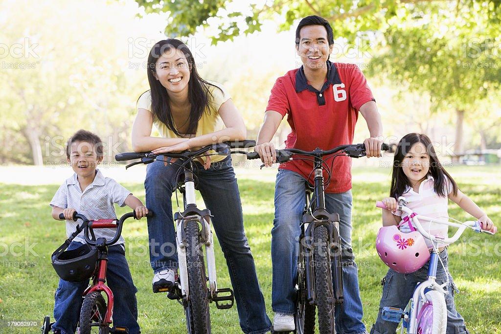 Family on bikes outdoors smiling stock photo