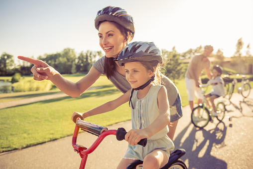 Happy family is riding bikes outdoors and smiling. Parents are teaching their children. Mom and daughter in the foreground