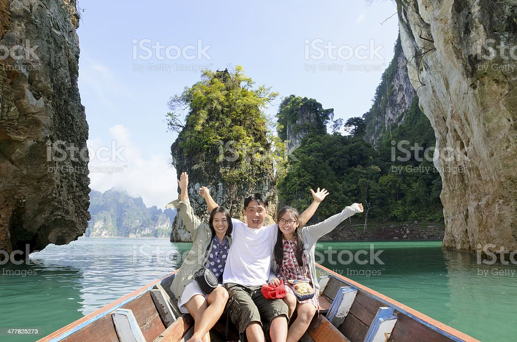 Family on boat in Khao Sok National Park, Thailand Happy family boat trip on summer vacation in Ratchaprapha Dam, Khao Sok National Park, Surat Thani Province, Thailand ( Guilin of Thailand ). Adult Stock Photo