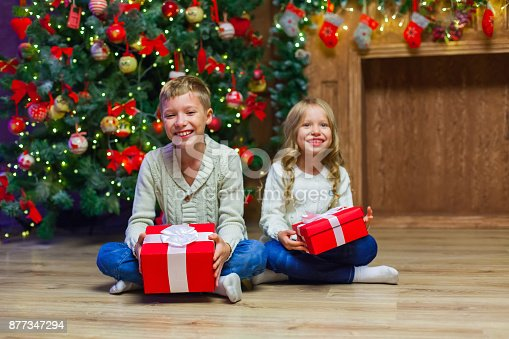 868220646istockphoto Family on Christmas eve at fireplace. Kids opening Xmas presents 877347294