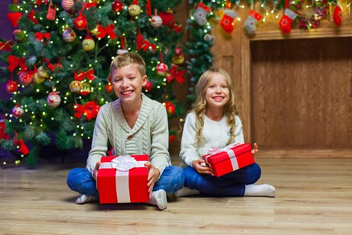 868220646 istock photo Family on Christmas eve at fireplace. Kids opening Xmas presents 877347294